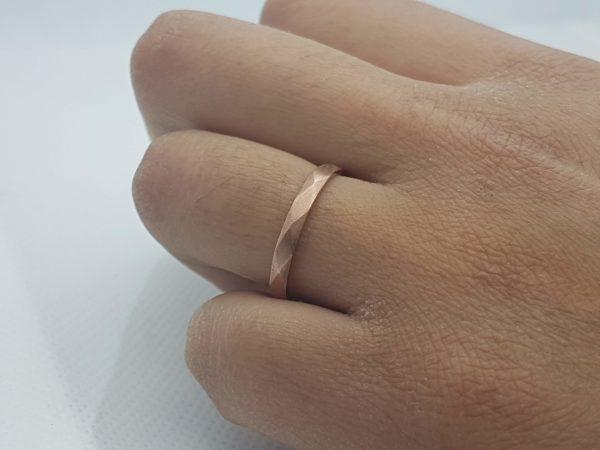 alliance à facettes regulières couleur cuivre sur main bronzée
