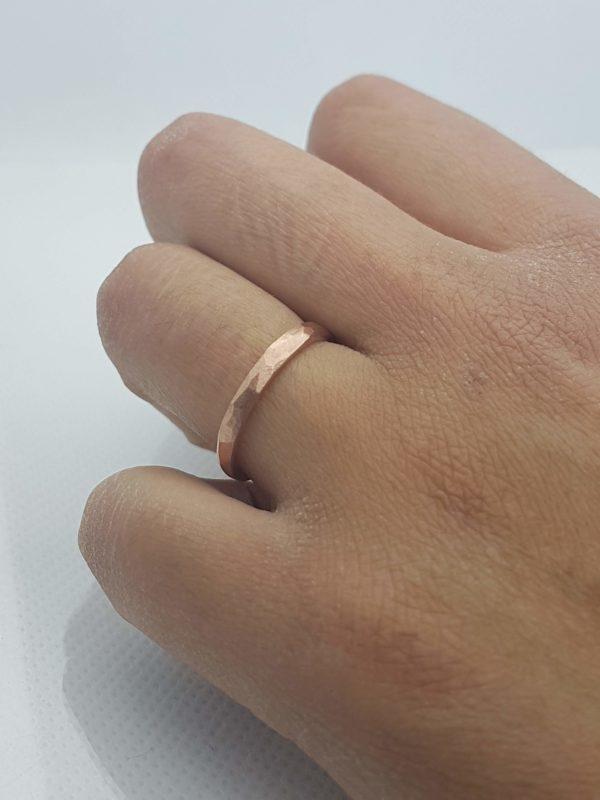 alliance à facettes irregulières couleur cuivre sur main bronzée